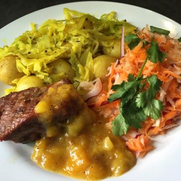 Costilla al horno con chutney de mango, col al curry y ensalada de zanahoria y rábano.